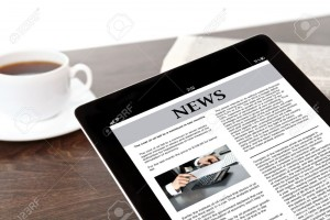 19091127-computer-tablet-with-business-news-on-screen-on-a-table-at-a-businessman-in-office-Stock-Photo